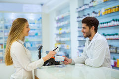 Experienced pharmacist counseling female customer Royalty Free Stock Image