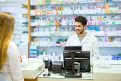 Experienced pharmacist counseling female customer in pharmacy royalty free stock photography