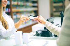 Experienced pharmacist counseling male customer in pharmacy. Experienced pharmacist counseling male customer in modern pharmacy and men pays with credit card royalty free stock image