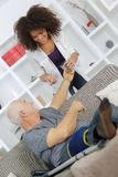 Experienced physician assisting senior man in recovery process. Experienced physician assisting her senior men in recovery process Stock Image