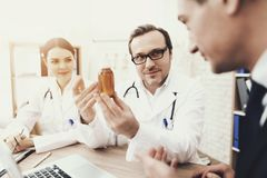 Experienced physician prescribes medicine for coughing to businessman in medical office. Adult men in business suit is being examined in clinic Stock Photos