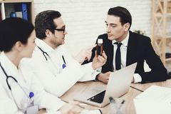 Experienced physician prescribes medicine for coughing to businessman in medical office. royalty free stock image