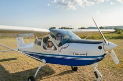 ROMA, ITALY - AUGUST 2018: An experienced pilot and a little girl child at the helm of a light-engine aircraft Tecnam P92 Echo. An experienced pilot and a little royalty free stock images
