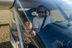 ROMA, ITALY - AUGUST 2018: An experienced pilot and a little girl child at the helm of a light-engine aircraft Tecnam P92 Echo. An experienced pilot and a little stock images