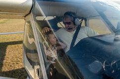 ROMA, ITALY - AUGUST 2018: An experienced pilot and a little girl child at the helm of a light-engine aircraft Tecnam P92 Echo. An experienced pilot and a little stock image