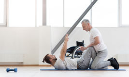 Experienced positive orthopedist assisting the disabled in the gym. Exercises for disabled in motion. Positive athletic aged orthopedist stretching the disabled Stock Photo