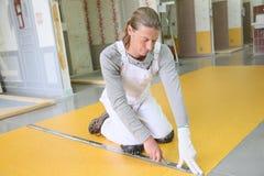 Experienced professional craftsman installing plastic flooring Royalty Free Stock Photo