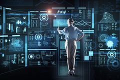 Experienced programmer pointing to the screen and looking elegant. Attention. Pleasant tall young programmer standing in front of a futuristic device and royalty free stock photography