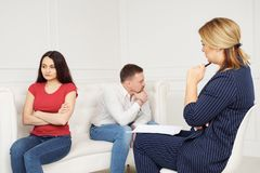 Experienced psychiatrist consulting a couple. Man and girl sit on the couch turned away from each other stock images