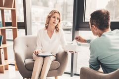 Experienced psychotherapist listening to her client. Listening to client. Experienced famous psychotherapist feeling concerned while listening to her client royalty free stock photo
