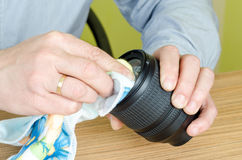 Experienced repairman fixes the camera lens. Cleaning lens glass Royalty Free Stock Image