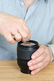 Experienced repairman fixes the camera lens. Stock Photography