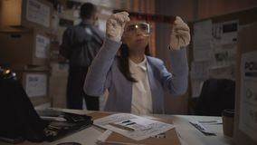 Experienced scientist looking at the criminal scene photos, drawing conclusions stock footage