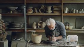 Experienced sculptor senior adult is making sculpture from clay ball on throwing wheel. He is watering clay to soften it. Experienced sculptor senior adult is stock video footage