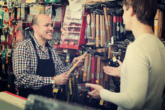 Experienced seller offering hammer to customer. Smiling elderly seller offering  hammer to client  in household store Royalty Free Stock Photography