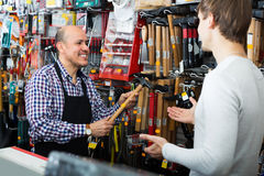 Experienced seller offering hammer to customer. Smiling elderly seller offering  hammer to client  in household store Royalty Free Stock Image
