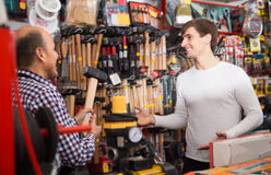 Experienced seller offering hammer. Experienced seller offering working tooling in household store Stock Images