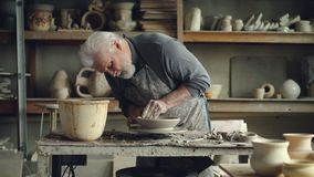 Experienced senior master is making low clay bowl on a pottery wheel in small workshop. Ceramics jigger, handmade. Experienced senior master is making low clay stock video footage