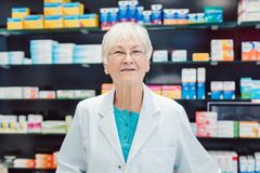 Experienced senior pharmacists in front of shelves in pharmacy royalty free stock images