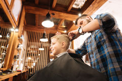 Experienced serious hairdresser combing the boys hair. Professional hairdresser. Experienced nice serious hairdresser holding a comb and combing the boys hair stock image