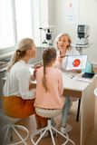 Experienced short-haired oculist being honest with her visitors. Carrying detailed poster. Experienced short-haired oculist being honest with her visitors while stock image