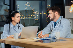 Experienced skillful doctors discussing work. Medical issues. Experienced skillful nice doctors sitting opposite each other and discussing work while working Stock Images