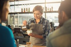 Experienced smiling barista making coffee to customers. Experienced barista in uniform making coffee to couple. Small business, occupation people and service stock photo