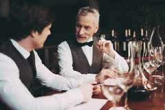 Experienced sommelier makes notes about taste qualities of wine drink sitting in restaurant. Wine tasting. Professional degustation expert in winemaking royalty free stock photo
