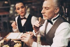 Experienced sommelier tastes aroma of wine from cork on corkscrew in restaurant. Wine tasting. Professional degustation expert in winemaking royalty free stock image