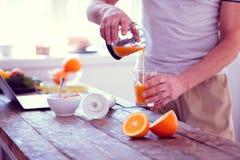 Experienced sportsman drinking orange juice in the morning every day. Morning juice. Experienced sportsman caring about his diet drinking orange juice in the stock image