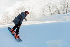 Experienced sportsman enjoying skateboarding outdoors. Side view full length photo. athlete performing tricks on a cold winter day. copy space royalty free stock photography