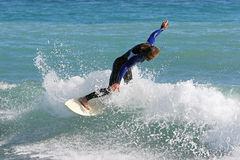 Experienced surfer carving an excellent wave. On vacation in sunny Spain Stock Photography