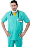 Experienced surgeon with hands on his waist. Male surgeon isolated over white background royalty free stock image