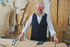 Experienced Tailor Making Bespoke Garments in Atelier. Portrait of skilled senior tailor looking at patterns while making clothes in atelier shop stock photo