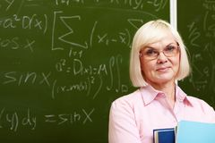 Experienced teacher. Charming older woman posing with a smile in front of the camera royalty free stock photo
