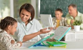 Experienced teachers working with children. In computer class stock photos