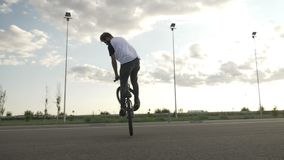 Experienced teen biker jumping and performing mid air maneuvers on his bike exercising freestyle tricks outdoor -. Experienced teen biker jumping and performing stock video