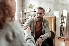 Mature and experienced therapist giving water to teenager. Experienced therapist. Mature and experienced bearded therapist giving water to teenager stock images
