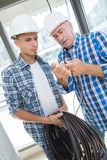 Experienced tradesman with new apprentice. An experienced tradesman with his new apprentice stock photography
