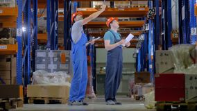 A warehouse inspector shows the cargo racks to a newbie. stock video footage