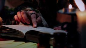Experienced witch reading spellbook, magic atmosphere and attributes, wizardy