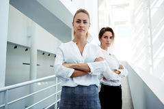 Experienced woman entrepreneur with partner posing in modern white office interior looking confident, Stock Image