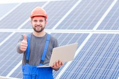 Experienced worker of the solar battery station holds a laptopand shows a thumbs-up gesture. stock photo