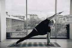 Experienced yoga man doing various poses indoors, panoramic city view at background.  Stock Image