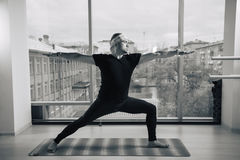 Experienced yoga man doing various poses indoors, panoramic city view at background.  Royalty Free Stock Image