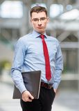 Experienced young accountant in blue shirt holds a laptop, portrait in office stock image