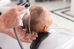 Experienced young barber is washing human head. Close up of hands of professional hairdresser. The man is making hairwash for small boy. The child is leaning on Royalty Free Stock Photo