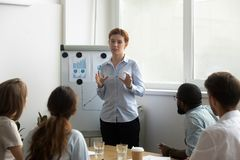 Business coach explaining corporate aims during seminar. Experienced young businesswoman business coach standing in front of audience speaking giving royalty free stock photos