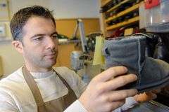 Experienced young cobbler looking at boot. Experienced young cobbler looking at a boot royalty free stock photos