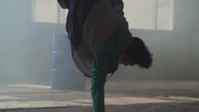 Experienced young hip-hop street dancer performing in front of large window in the dark abandoned building. Contemporary stock footage